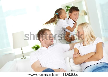 Portrait of young couple looking at one another with two children playing on background