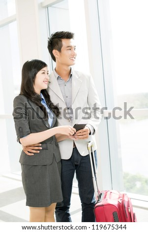 Portrait of young couple looking through window in airport - stock photo