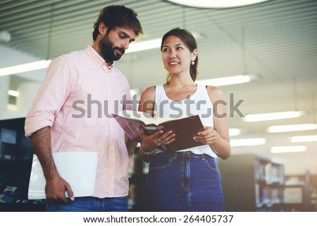 Portrait of young couple of students holding some books while preparing for university exams, business colleagues having fun while standing in modern work space, classmates studying in library, flare