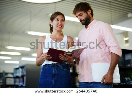 Portrait of young couple of students holding some books while preparing for university exams, business colleagues having fun while standing in modern work space, classmates studying in library - stock photo