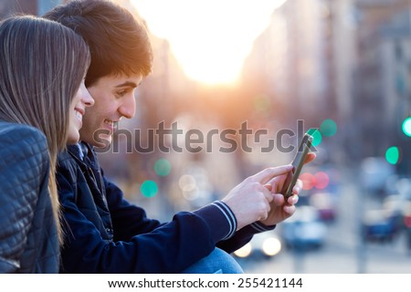 Portrait of young couple of tourist in town using mobile phone.  - stock photo