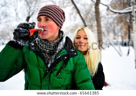 Portrait of young couple outdoor. Resting together in winter park