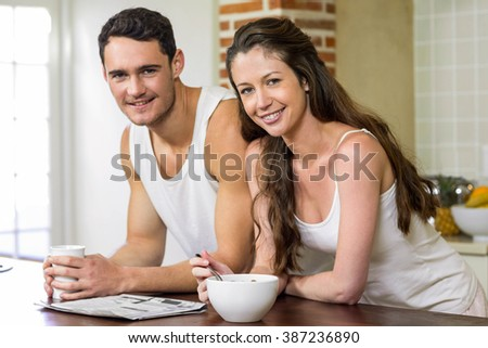 Portrait of young couple reading newspaper while having breakfast in kitchen