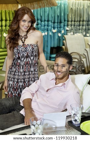 Portrait of young couple shopping for sofa in store