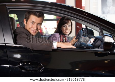 Portrait of young couple sitting in a new car at showroom - stock photo