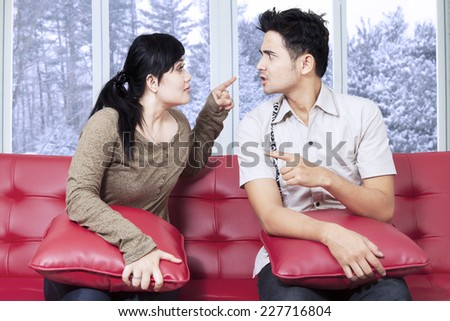 Portrait of young couple sitting on sofa and quarreling at home with winter background on the window - stock photo