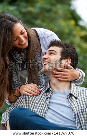 Portrait of young couple smiling at each other in park. - stock photo