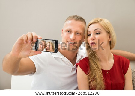 Portrait Of Young Couple Taking A Selfie With Mobile Phone - stock photo