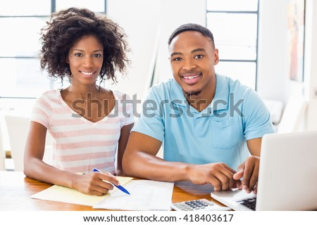 Portrait of young couple using laptop while checking bills