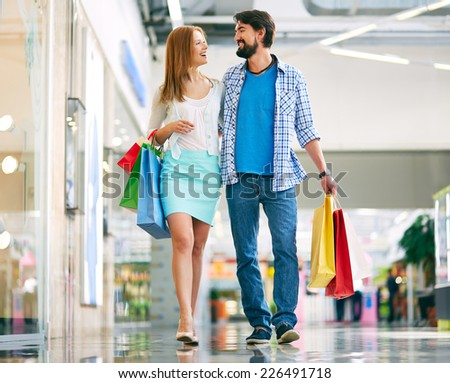 Portrait of young couple walking down the mall and talking - stock photo
