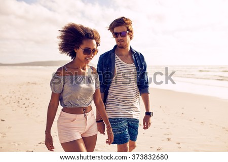 Portrait of young couple walking on the beach. Young man and woman strolling on the shoreline during the summertime. - stock photo