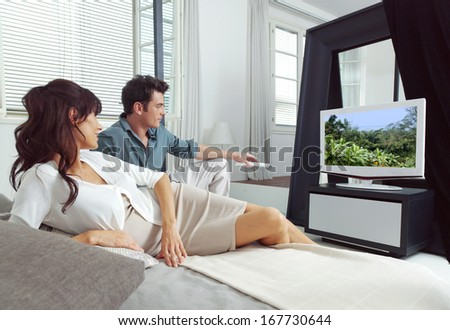 Portrait of young couple watching tv lying on bed  - stock photo