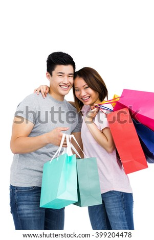 Portrait of young couple with shopping bags on white background