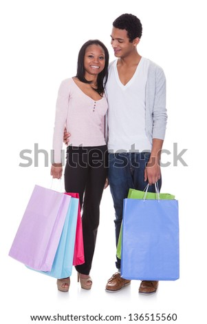 Portrait Of Young Couple With Shopping Bags Over White Background
