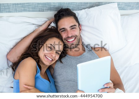 Portrait of young couple with tablet while lying on bed in room