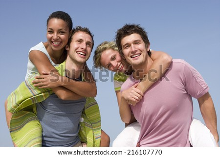 Portrait of young couples at beach - stock photo