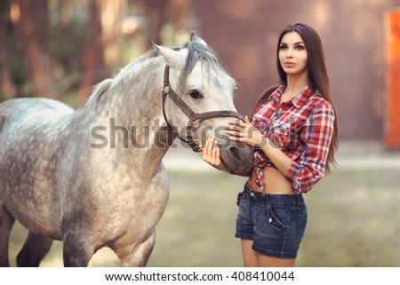 Portrait of young cowgirl and white horse outdoors - stock photo