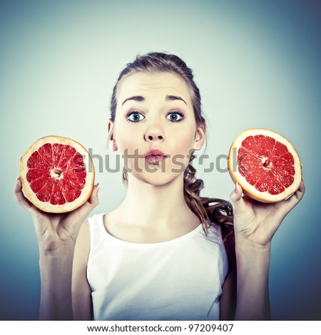 portrait of young crazy woman with grapefruit