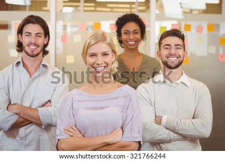 Portrait of young creative business team with arms crossed in office - stock photo
