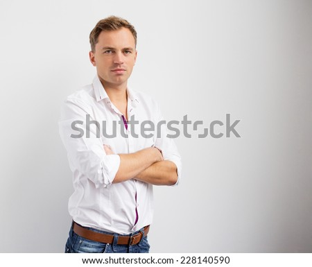 Portrait of young creative man standing with arms crossed - stock photo