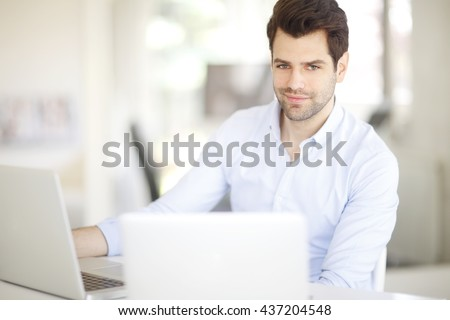 Portrait of young creative professional man working on laptops while sitting at his workstation.