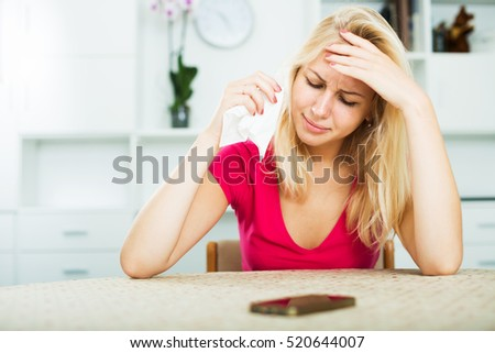 Portrait of young crying girl waiting for call sitting indoors