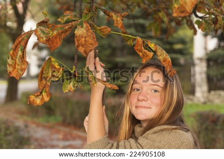 Portrait of young cute girl in autumn park