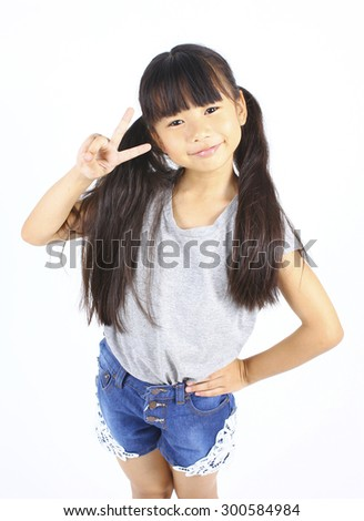 Portrait of young cute girl posting with two fingers. - stock photo