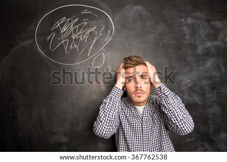 Portrait of young cute man with expression of pain on his face - stock photo