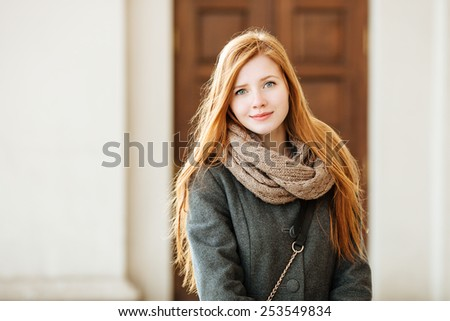 Portrait of young cute redhead lady wearing coat and scarf posing outdoors with architectural background - stock photo