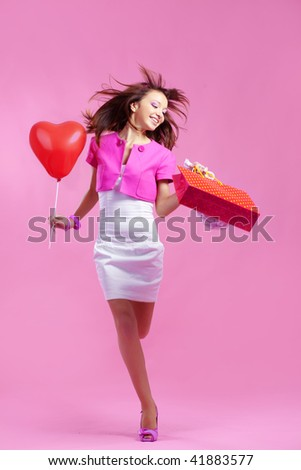 Portrait of young cute shopaholic girl running on pink studio background
