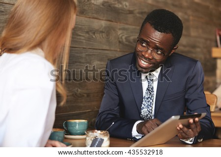 Portrait of young dark-skinned professor in glasses and elegant suit sitting at a coffee shop with his Caucasian student, using tablet for explaining a new material, looking and smiling at the girl - stock photo