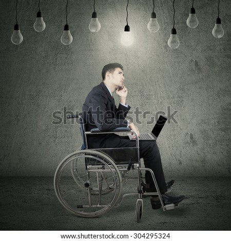 Portrait of young disabled businessman sitting on wheelchair under lamps while holding laptop and thinking idea - stock photo
