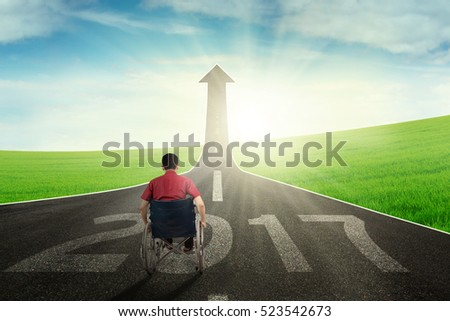 Portrait of  young disabled man using a wheelchair on street with numbers 2017 while looking at road shaped arrow upward