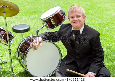 Portrait of young disabled musician next to drums outdoors. - stock photo
