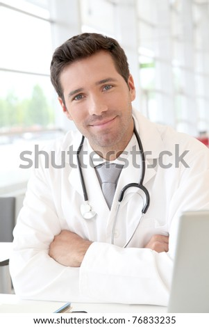 Portrait of young doctor at work - stock photo