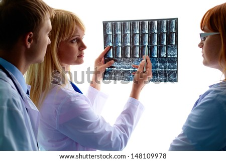 Portrait of young doctor showing and interpreting x-ray to colleagues - stock photo