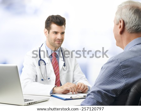 Portrait of young doctor sitting at desk with elderly patient while check up and write diagnosis.