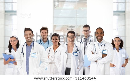 Portrait of young doctors and nurses at medical center, all smiling.