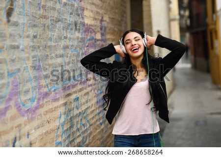Portrait of young dominican woman in urban background listening to music with headphones - stock photo