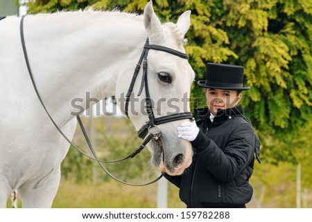 Portrait of  young dressage rider with big sport horse - stock photo