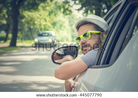 Portrait of young driver wearing sunglasses in driverâ??s seat. Vacation and travel concepts.
