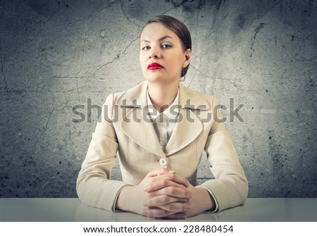 Portrait of young elegant businesswoman sitting at table - stock photo