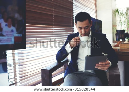 Portrait of young elegant men reading e-book on his digital tablet while drinking beverage in cafe inside, confident businessman using touch pad for remote work while enjoying rest during coffee break - stock photo
