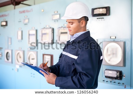 Portrait of young engineer taking notes at control room - stock photo