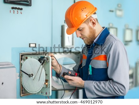 Portrait of young engineer working at control room in factory