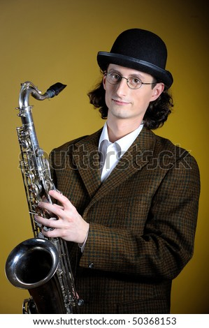 portrait of young english gentleman in bowler hat holding saxophone. yellow background