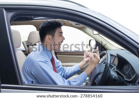 Portrait of young entrepreneur looks angry in the car while showing two middle fingers and shouting - stock photo