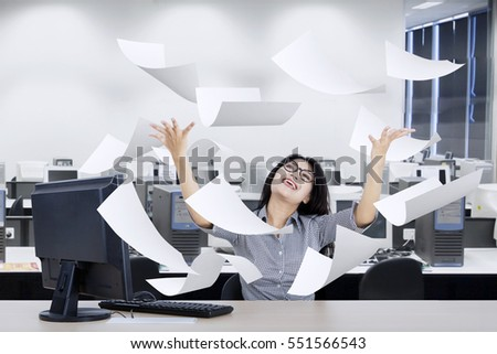 Portrait of young entrepreneur raising her hands while looking paper flying over her head