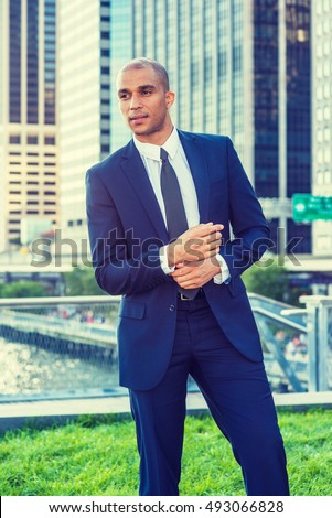 Portrait of Young European Businessman in New York. Wearing blue suit, white shirt, black tie, Mixed Race French guy with shaved head stands in business district, hand touching cuff, going to work.